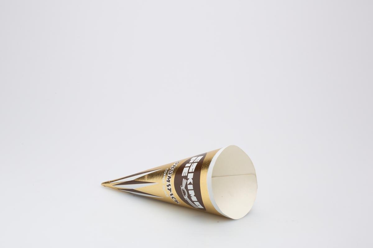 Kjegleformet iskrempapir (kremmerhus) i aluminium og papir. Kremmerhuset er med farger på utsiden, og uten farge (hvit) på innsiden. Kremmerhuset har gullfarget bakgrunn, med hvite og brune vertikale striper nederst, ser ut som avlange romber.