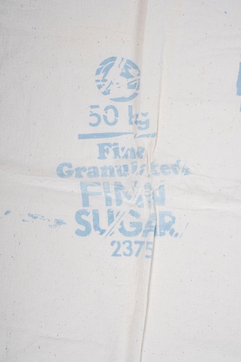 Putevar sydd av sukkersekk. Det er åpning i den ene kortenden. Åpningen er revet opp.