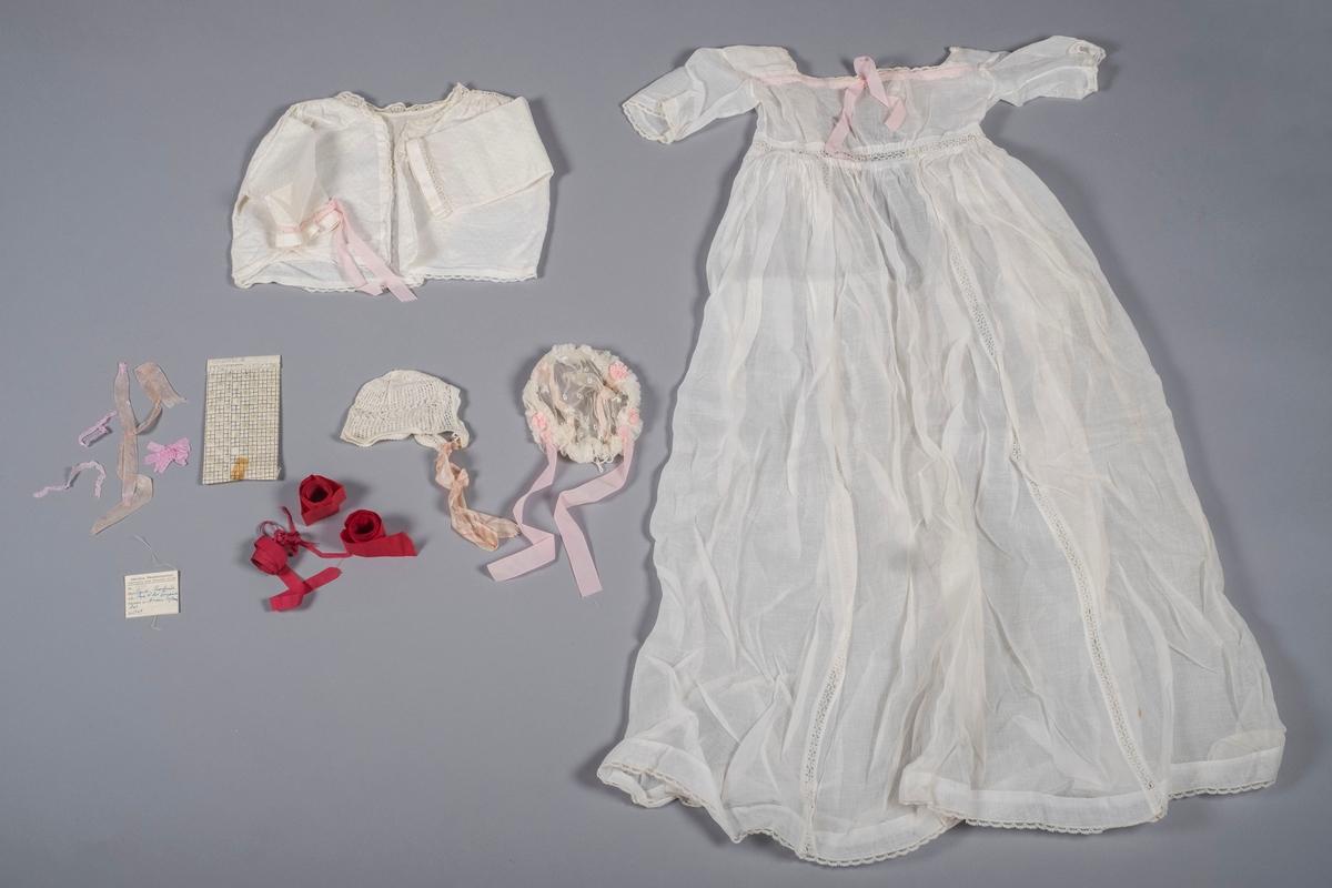 Dåpskjole med jakke, to luer og ekstra bånd, samt en papirlapp fra Akershus Bondekvinnelags Tekstilutstilling ved Norsk Folkemuseum i 1953, hvor kjolen var stilt ut.   Dåpskjole i hvit musselin med kniplinger. To loddrette felt med kniplinger på skjørtet, samt kniplinger rundt livet. Hvit blonde i halskant, rundt mansjettene, og rundt skjørtekant. Rosa bånd i halslinningen, som ikke er originale. Åpning bak, ingen lukkemekanisme. Trolig lukket med sølje. Brukt første gang ved Hans Bernhard Præsteruds dåp i 1867.  Jakke til dåpskjole i hvitt mønstret bomullstekstil. Åpen i front, ingen lukkemekanisme. Blonder i halskant, langs åpning, og langs nedre kant. Kniplinger i skuldre, og mellom mansjett og erme. Det er festet et rosa bånd i knipling på venstre arm, båndet er ikke originalt.  Dåpslue i hvitt bomullsgarn. Trolig strikket. Snurpet og sydd sammen på baksiden. Strikket kan sydd på i nakkelinningen. Originale knytebånd i silke, rosa og hvit-stripede.  Liten dåpslue i hvitt og rosa. Nettinglue, gjennomsiktig, med broderte motiver i hvit bomullstråd. Kreppede kanter rundt ansikt og nakke. Det er festet to blomster av samme materiale som øvrige bånd på hver kant av ansiktet, totalt fire stykker. To smale pyntebånd følger luens form på bakre side. Sydd inn på vrangsiden. Rosa pyntebånd i polyester. Sydd inn en hvit bomullstråd i nakkekant for å snurpe sammen luen i nakken.  Originale bånd til dåpskjole. 5 røde bånd i diverse størrelser, 2 brede, 1 mellombred og to smale.  Papirlapp fra utstilling av dåpskjolen på Norsk Folkemuseum i 1953. Rektangulær, brettet i to, med skrift på fremsiden. Opplysninger om hvem som eier dåpskjolen, hvor eier bor, hvem som har produsert den, og når den er produsert. Har vært sydd på kjolen, merker etter nål og rester av tråd på baksiden.