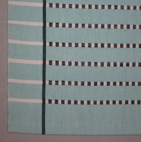 """Randig duk, tre stycken, vävd i tuskaft med ränder i inslagsflottering av tvåtrådigt bomullsgarn. En duk är blågrön (turkos) en rosa och en gul. Varpen är blekt med en smal svart rand i varje sida 45 mm in från kanten. Tuskaftsinslaget är färgat med blekta smala ränder med svarta flotteringar. De färgade tuskaftsränderna är 20 mm breda och de blekta 5 mm. De svarta flotteringarna bildar rutor  på de blekta ränderna, men är vävda endast mellan de svarta ränderna i varpen, vilket ger endast blekta ränder i sidan. Alla tre dukarna har smala tråcklade fållar.  Den första duken är blågrön (turkos) och är märkt med R7:1 på ett vitt bomullsband. I ena hörnet är en pappersetikett fastsatt med häftklammer. Texten lyder: """"DUK FLOTT BOMULL MODELL"""". En gul prick med ett S är klistrat på etiketten. På andra sidan av etiketten är det en tryckt spånfågel med texten """"LÄNSHEMSLÖJDEN SKARABORG SKÖVDE - LIDKÖPING"""". Den andra duken är rosa och är märkt med R7:2 på ett vitt bomullsband. I ena hörnet är en pappersetikett fastsatt med häftklammer. Texten lyder: """"DUK FLOTT BOMULL MODELL"""".På andra sidan av etiketten är det en tryckt spånfågel med texten """"LÄNSHEMSLÖJDEN SKARABORG"""". Den tredje duken är gul och är märkt med R7:3 på ett vitt bomullsband. I två av hörnen är pappersetiketter fastsatta med häftklammer. På den ena lyder texten: """"DUK FLOTT BOMULL TVÄTT 60 90 X 90 S 290:-"""". På andra sidan av etiketten är det en tryckt spånfågel med texten Länshemslöjden Skaraborg. På den andra etiketten lyder texten: Duk FLOTT Bomull, Ann-Mari Nilsson, tvätt 60, S 298:-.  På andra sidan av etiketten är det en tryckt spånfågel med texten Länshemslöjden SKARABORG SKÖVDE"""".  Duken med modellnamnet Flott är formgiven av Ann-Mari Nilsson och tillverkad av Länshemslöjden Skaraborg. Den finns med  på sidan 22-23 i vävboken Inredningsvävar av Ann-Mari Nilsson i samarbete med Länshemslöjden Skaraborg från 1987, ICA Bokförlag. Se även inv.nr. 0001-0006,0008-0040."""