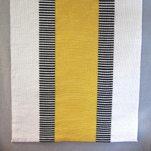 """Löpare, tre stycken, vävd i tuskaft och varptvist. Löparen har ett 130 mm brett enfärgat mittparti i blått, rött eller gult med ett 45 mm brett tvärrandigt tvistparti i svart och blekt på vardera sidan. Ytterkanten är blekt och 85 mm bred. Varpen är blekt, svart och färgat i tvåtrådigt bomullsgarn och inslaget i halvblekt lintow. Löparen med gult mittparti är 380 mm bred och 1095 mm lång, den röda är 380 mm bred och 1340 mm lång och den blå är 380 mm bred och 850 mm lång.  Den blå och den röda löparen är märkt med ett vitt bomullsband med texten: """"DANS"""" Ann-Mari Nilsson.  Löparen med modellnamn Dans är formgiven av Ann-Mari Nilsson och tillverkad av Länshemslöjden Skaraborg. Den finns med  på sidan 32-33 i vävboken Inredningsvävar av Ann-Mari Nilsson i samarbete med Länshemslöjden Skaraborg från 1987, ICA Bokförlag. Se även inv.nr. 0001-0011,0013-0040."""