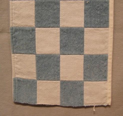 Ett täcke i babystorlek i mjuk men stadig kvalitet. Varpen är av blekt bomullsgarn 16/2 och inslaget av blekt bomullsgarn 8/2 och gråblått velourgarn. Dubbelväv i tuskaft i ett rutmönster. Dubbelväven är öppen i stadkanten. Provet är 4 rutor brett och 11 rutor långt.  Se även inv.nr.0033:1 Täcke med rosa velourgarn i inslaget.  Vävprovet är märkt med R32:2 på ett vitt bomullsband.  Vävprov med modellnamn Sammet är formgivet av Ann-Mari Nilsson och tillverkat av Länshemslöjden Skaraborg. Det finns med  på sidan 78-79 i vävboken Inredningsvävar av Ann-Mari Nilsson i samarbete med Länshemslöjden Skaraborg från 1987, ICA Bokförlag. Se även inv.nr. 0001-0032,0034-0040.