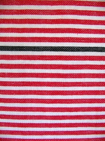 Randigt vävprov vävt i korskypert med varp i cottolin och inslag av entrådigt lingarn. Det är ett 155 mm brett blekt parti i vardera ytterkanten. Ränderna i mitten är röda med en svart rand på en tredjedel. Vävprovet har en smal tråcklad fåll i ena sidan.Vävprovet är formgivet av Ann-Mari Nilsson och tillverkat av Länshemslöjden Skaraborg.