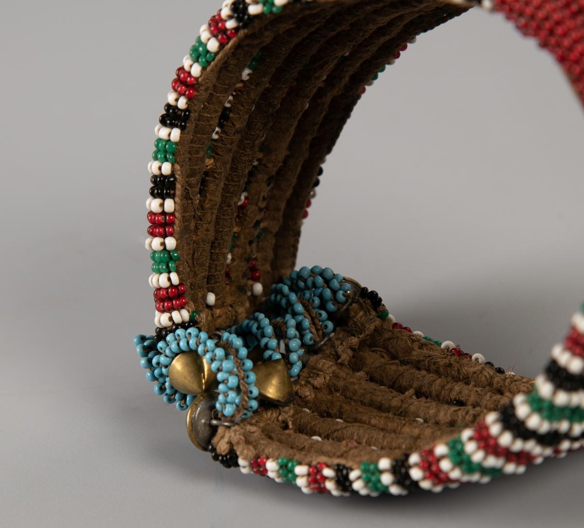 Bredt, tett perlebesatt bånd med syv perlesnorer festet på  hyssing. På midten er det et felt med bare røde perler. På hver side av dette er det vertikale striper i sort, grønt og rødt, hver stripe avgrenset av en  rad hvite  perler. I hver ende fem snurrebassformede   messing  knapper, som lukkes med lyseblå perlehemper.