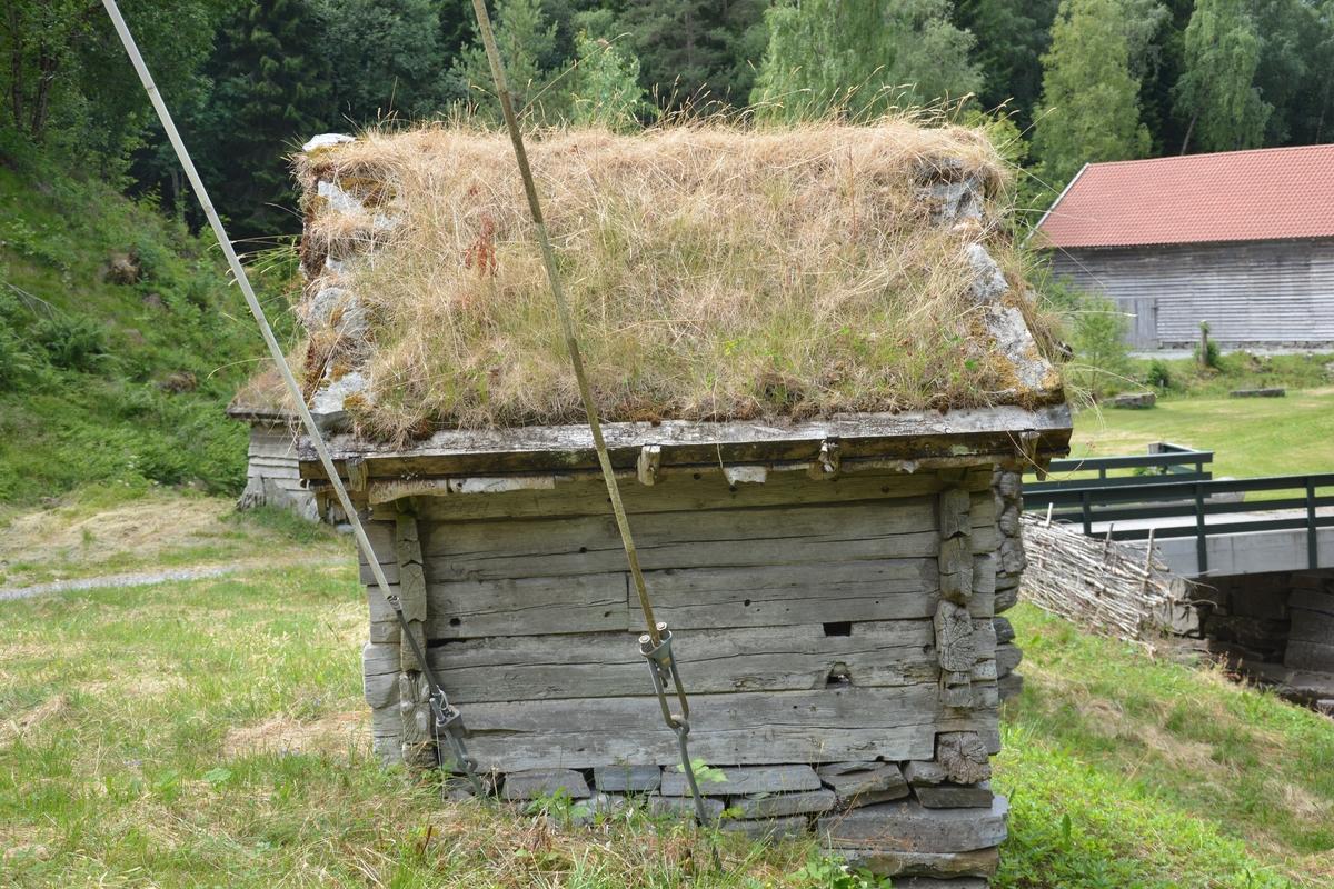Tømra liten bygning (1 rom), delvis med supanel utvendig.  Tørrmur og torvtak Tosetar