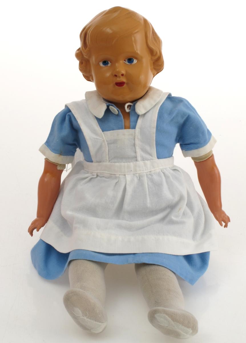 Dukke med dukkeklær, bærebag samt kuffert med flere dukkeklær. Dukken er ved innkomst kledd i sykepleieruniform.   DELER:  a. Dukke Hode og hender/armer av celluloid. Resten av tekstilt materiale.  b. Bærebag til dukke Av plast, sky. Rosa farge med glidelås. Nyere enn dukke og kuffert.  c. Koffert (med dukkeklær ved innkomst)  Kuffert av tykk kartong. Sydd sammen. Lærhempe til hengsler. Handtak festet med metallbeslag.  d - z  Dukkeklær