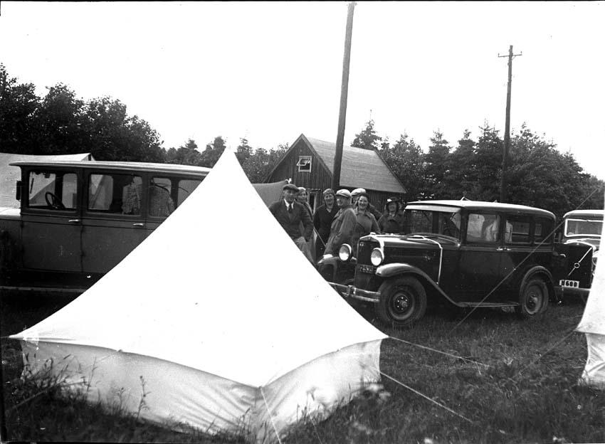 En grupp personer, tält och bilar på en camping.