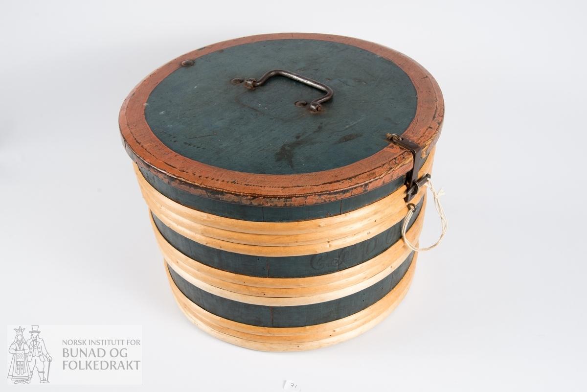 Bomme, krunebomba.  Bomme i tre med smijernsbeslag. Bøkket som en tønne. Tre tredobbelte rader bånd. Malt mørk grønn, naturfarga bånd, rød kant rundt lokket. Skrevet på utsiden: CT/G?DO 1827. Innskåret rose under. Foret med håndskrevne dokumenter av papir, et datert april 1799. Kan være handelsdokumenter. Høgde 25 cm. Diameter 37 cm. Bredde band 1,5 cm.