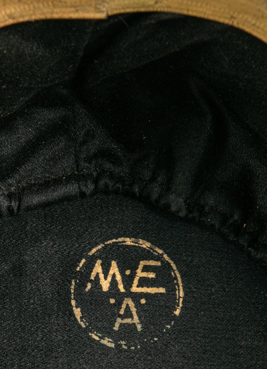 Del av paraduniform modell ä/1886. Mössa med stor mässingsplåt framtill med lilla riksvapnet, lejon med mera, ståndarknapp med dubbelt monogram G V, samt svart tagelplym.