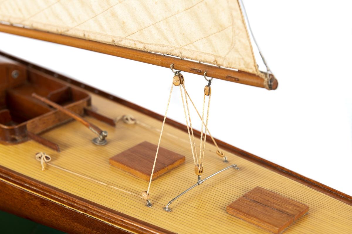 Fartygsmodell av skärgårdskryssaren EBELLA Marconirigg med mast, fock och storsegel av bomull. Sitt och styrrum, rorkult, två luckor, skotlevang.  NAMN1921-1991 1921EBE 1922-EBELLA -1930 1931Saknas 1932-EBELLA 1933EBELLA 1937RIAN omriggad till 120 m2 1943BOMSAN II 1946saknas 1947BEATRICE-AURORE 1991BEATRICE-AURORE