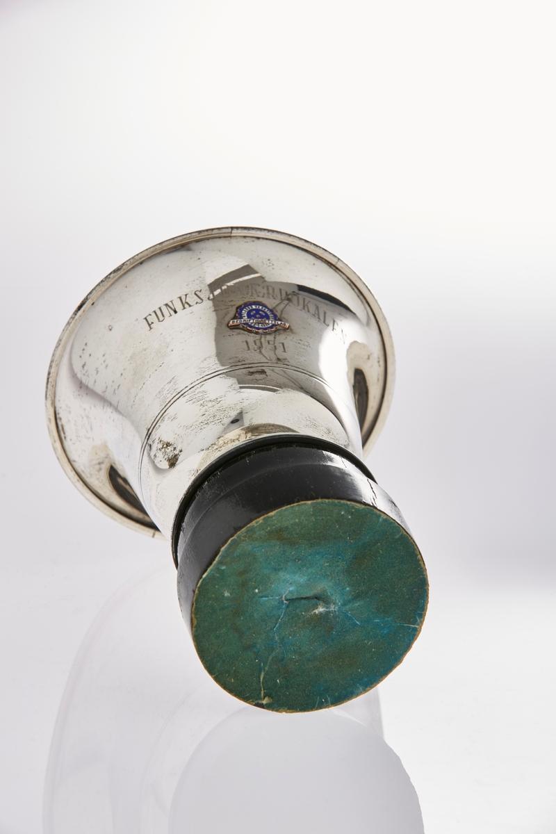 Emblem: Sirkulært med tagger, hvit og blå emalje med bronsebokstaver. Bokstaver: Nylands verksted 22.1.1926 Bedriftsidrettslag