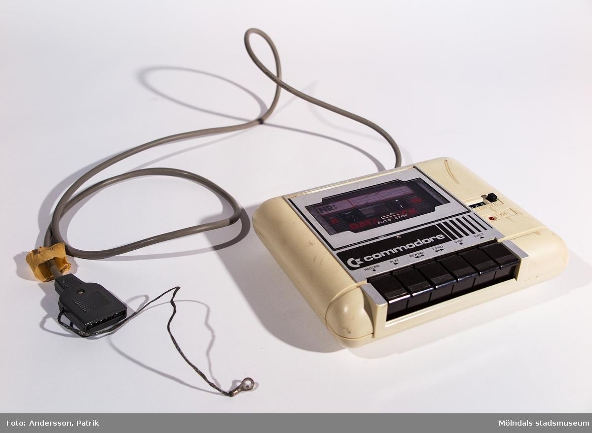 Kassettenhet, C2N CASSETTE. Beigefärgat plasthölje med logotypen Commodore. Svarta knappar och räknare.