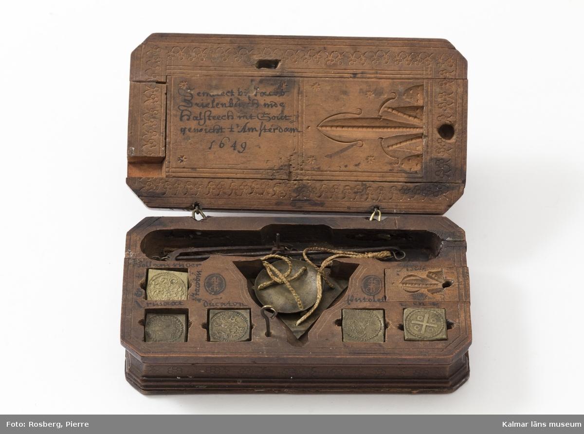 KLM 14592 Myntvåg med vikter i etui. Etui av trä med stämplad och skuren dekor. I själva lådan fack för vågen samt för 5 vikter, (det ligger två vikter i facket överst till vänster), under ett skjutlock fack för tunna vikter, 2 stycken finns bevarade. I lådans undre del har funnits en utdragslåda, förkommen. I locket ett utdragslock, varunder fack för 10 vikter, varav två är förkommna. Flera av vikterna daterade 1748 på baksidan. I locket signerad:---Amsterdam 1649.