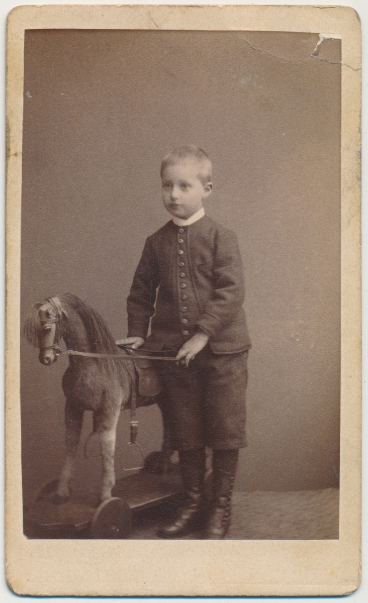 Helfigur foto av liten gutt med lekehest, ukjent