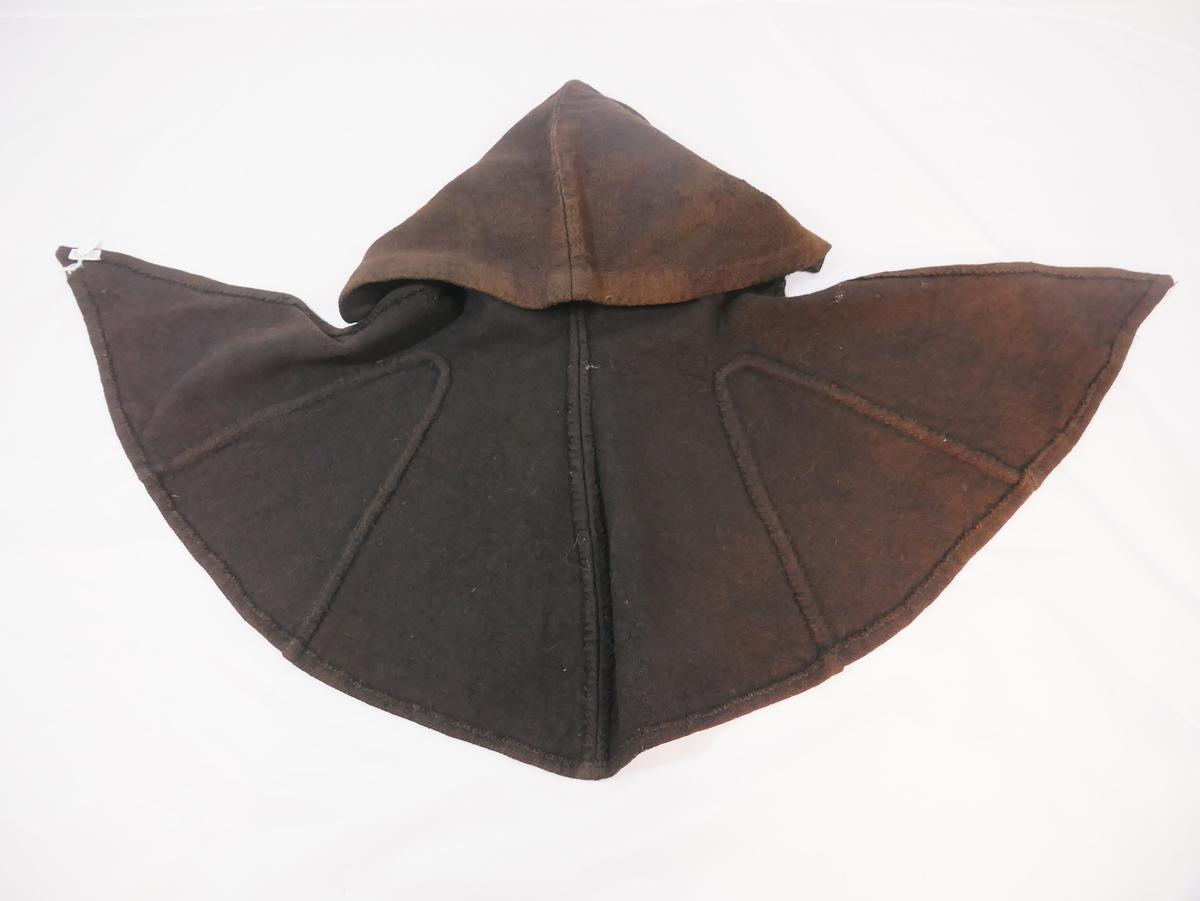 Hette med skulderslag, sydd av to stykke med kilar i begge sidene. Fald rundt hetta.