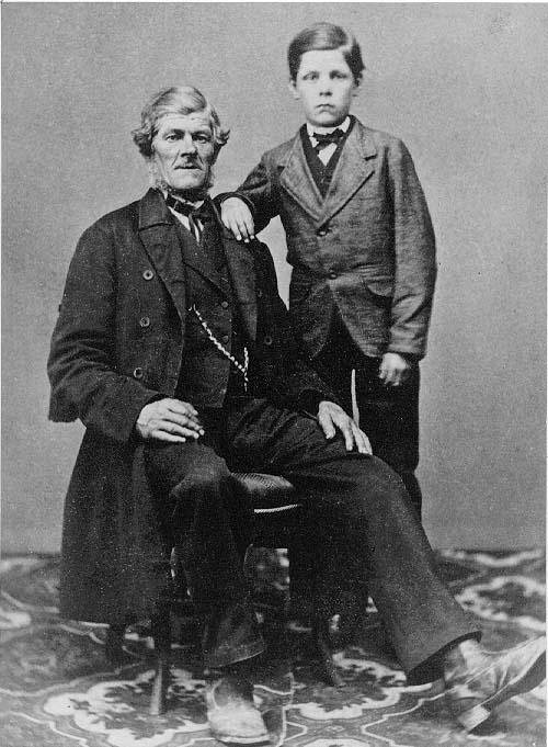 En äldre man sitter på en stol. En pojke står intill med sin högerarm vilande på mannens vänstra axel. Det är far och son.