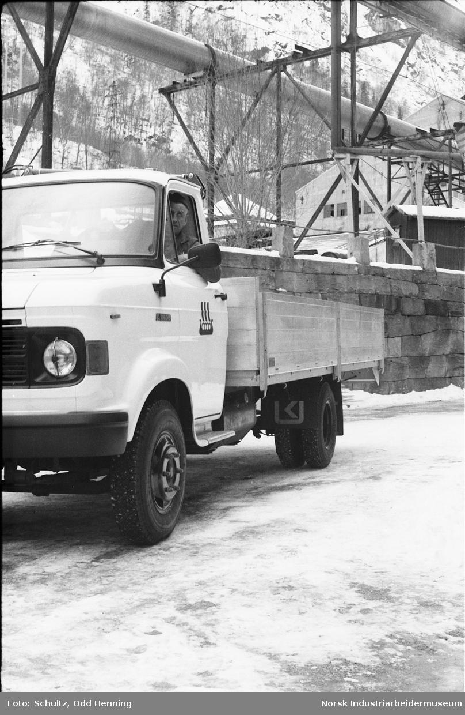 Mann sitter inn i lastebil merket Norsk Hydro, bygg/anlegg.