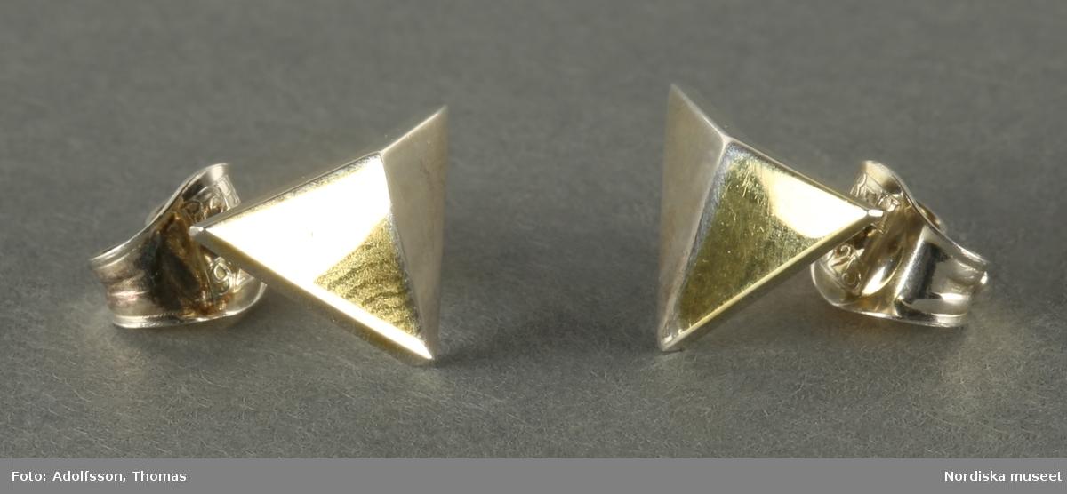 a:1, b:1) Silverörhängen, ett par, i form av svagt konvex trehörning. Örhängena är delvist guldpläterade på framsidans ena halva. Örhängena fästes vid örat medels stift samt ett bakstycke, a.2, b:2) sk snurrebuss, som förhindrar örhängena att ramla av.  Örhängena är stämplade AC Hultberg på baksidan.  /Cecilia Wallquist 2019-02--21