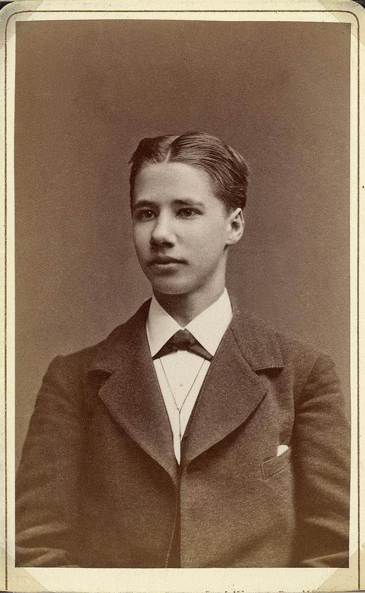Porträttfoto av en ung man i mörk kavaj, vit skjorta och fluga.  Bröstbild, halvprofil. Ateljéfoto.
