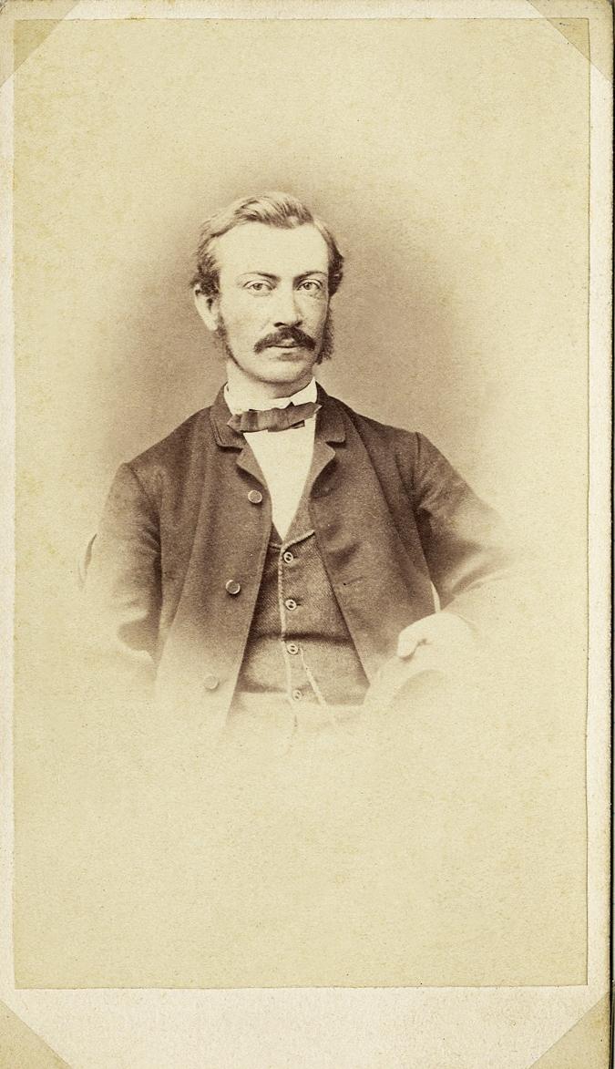 Foto av en man med mustascher, klädd i kavajkostym med väst, stärkkrage och fluga. På västen skymtar en klockkedja. Midjebild, halvprofil, Ateljéfoto.