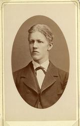 Foto av en ung man i kavajkostym med väst, stärkkrage och fl