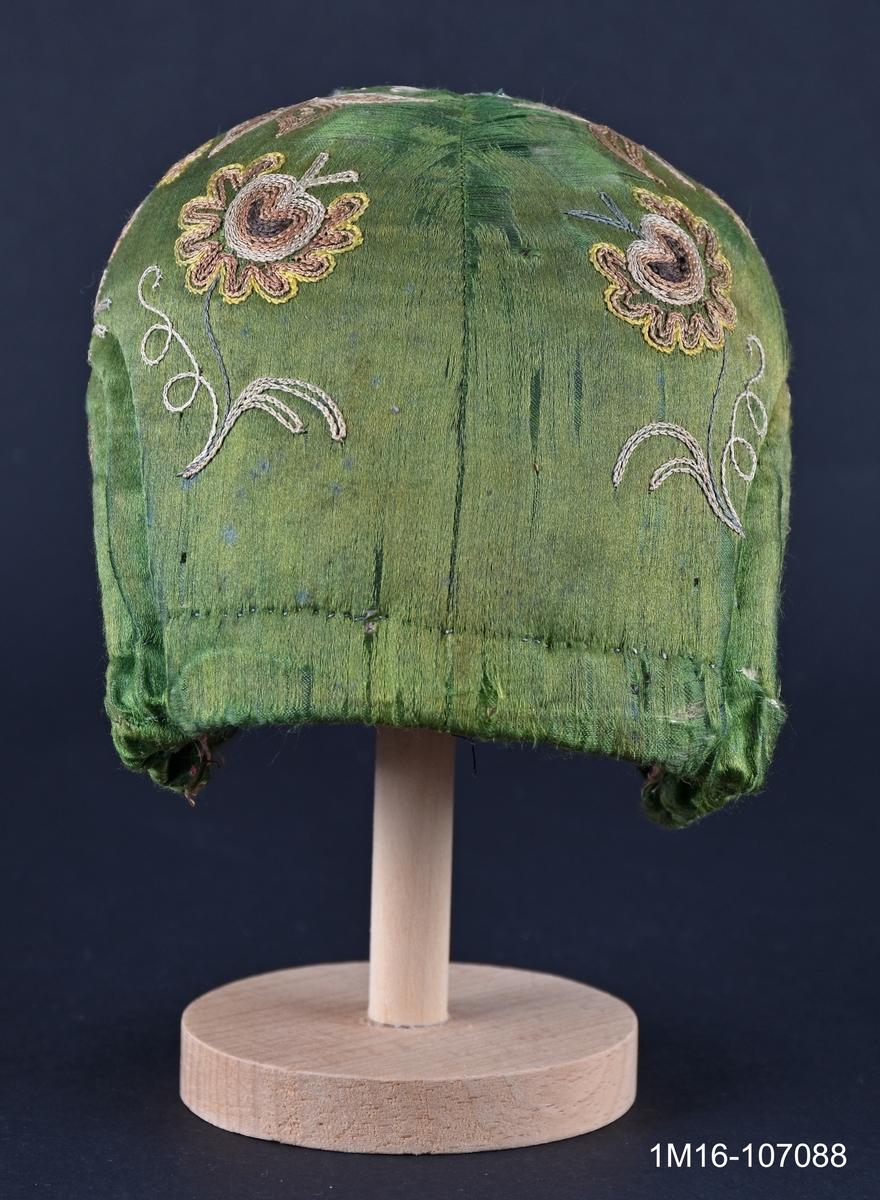 Bindmössa av grönt siden med gulbrunt tambursömsbroderi i bruna nyanser. Bindmössan kopierades till Valledräkten under 1960-talet av ett dräktråd. Har tillhört Carolina Johansson (1835-1917).