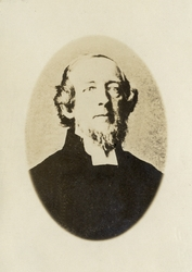 Foto av en man med pipskägg, klädd i prästrock och prästkrag
