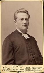 Foto av en man klädd i prästrock och prästkrage. Bröstbild,