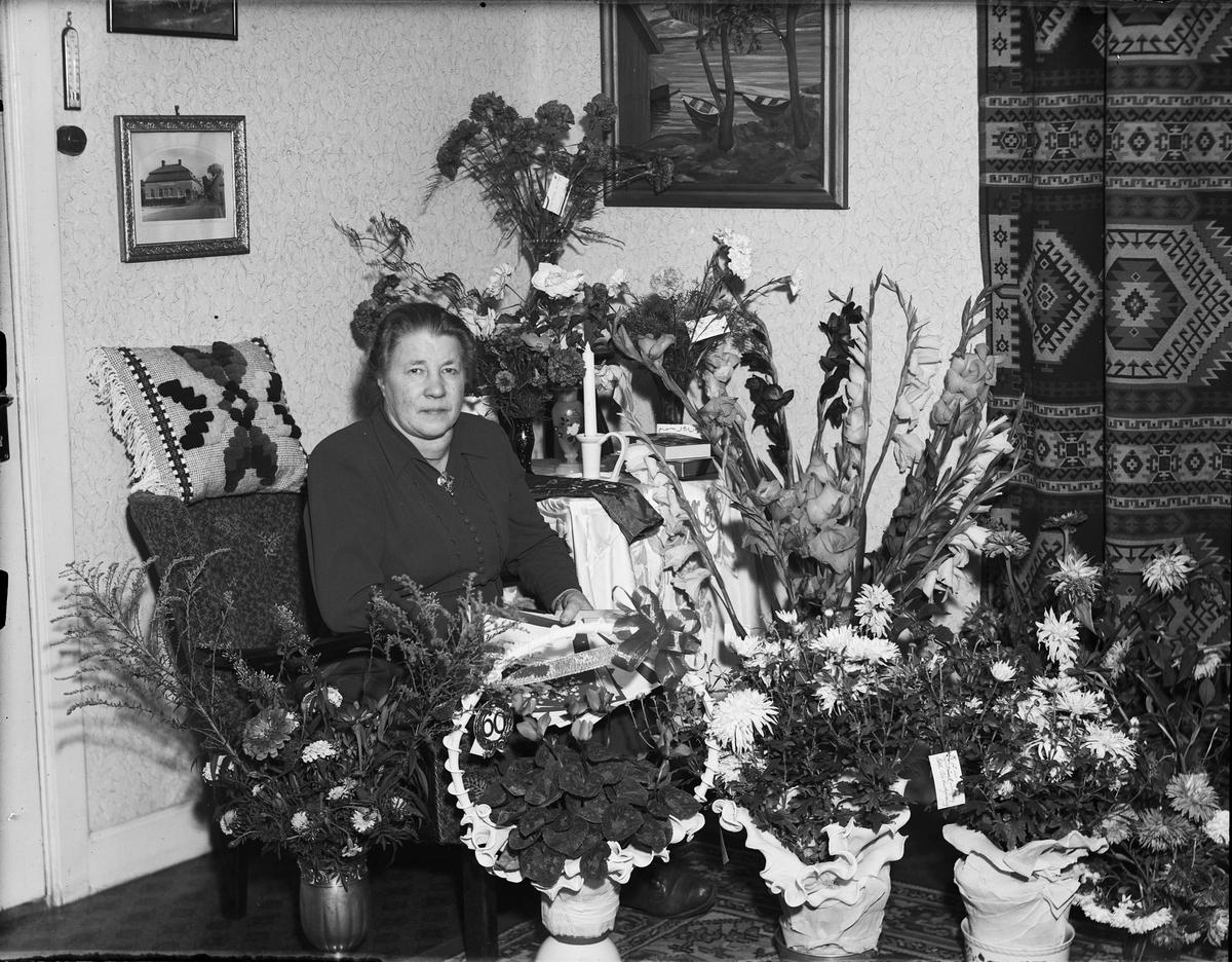 Kvinna i hemmet omgiven av blommor, firar 60-årsdag, Östhammar, Uppland