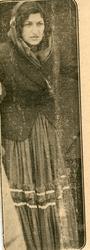 Porträtt av en kvinna iförd kjol, dikhlo och kavaj. Bildens