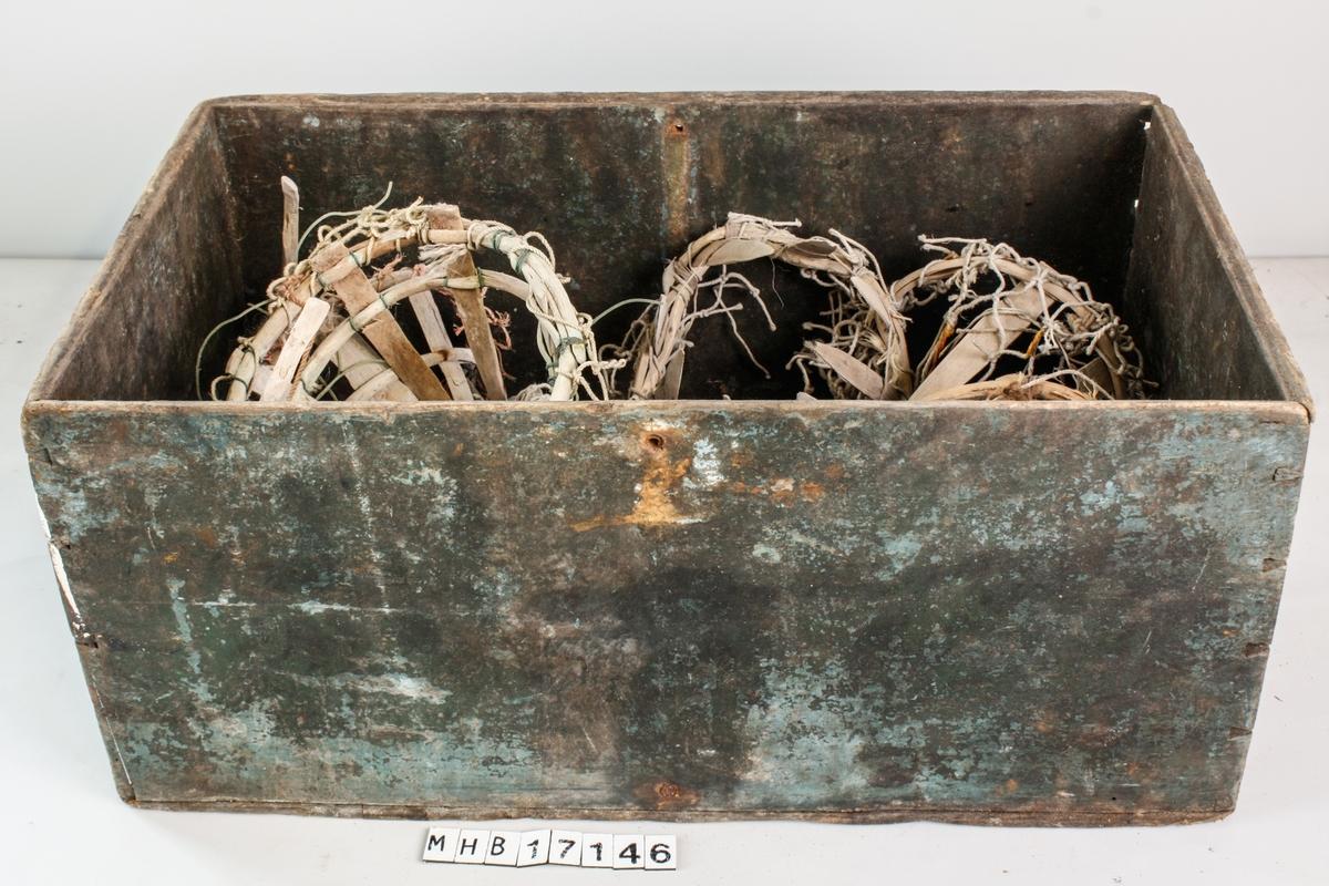 Liten kasse fylt med syv ødelagte kalver, to spiker og fireavknekte pinner til kalver. Kassen er satt sammen av ett bord i hver side og ett bord i bunn som nå er sprukket. Bordene i siden er sammenføyd med svalehaleskjøt, bunnen er spikret. Kassen har rester av å ha bvært bemalt. Den har to malingslag, det underste er grønt/blått og det øverste grått. Malingslaget er delvis avskallet. rester av malingssøl i andre farger, sort og rødt er også tilstede. Kalvene består av spissede, flate trepinner, sannsunligvis av einer festet til en ring. Med rester av buss (garn) rundt. fem av de syv kalvene mangler pigger. En av kalvene er festet med nylontråd og to av dem har kobbertråd.