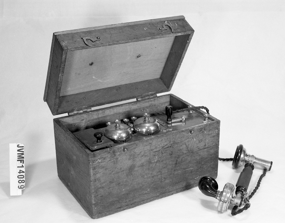 Linjetelefon i trälåda, med två ringklockor samt telefonlur med bakelitdelar.