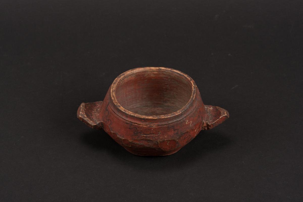 Rund, svarvad, träskål med två handtag. Målad i rött med ornamentala våglinjer i gult och svart. På undersidan ett inristat K.