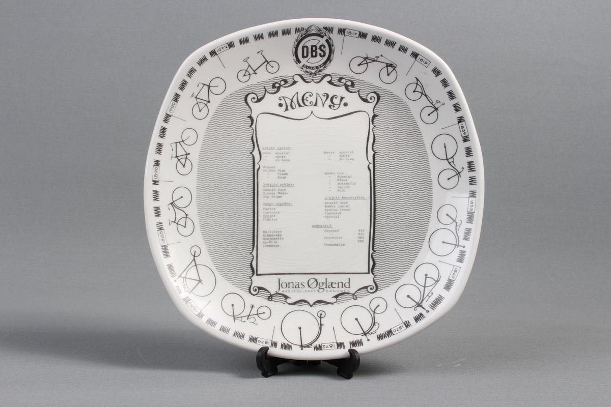 Jubileumstallerken med tekst som gir en beskrivelse av historikken. Med to hull på baksiden for oppheng.