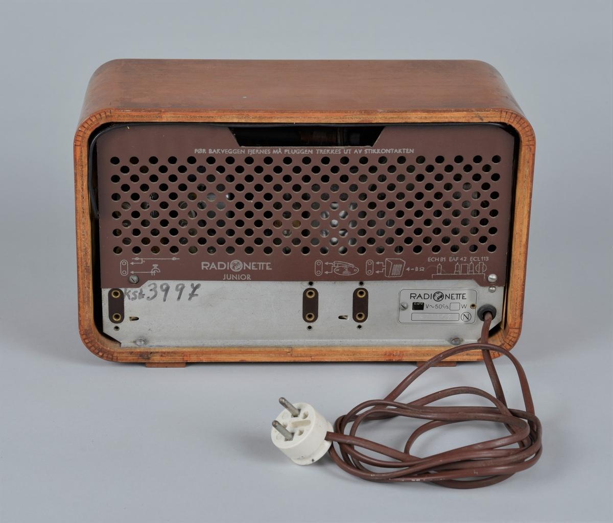 Radiomottaker for kort-/mellom- og langbølgemottak.  På bølgebryteren til høyre er det 4 bokstaver- L M F K - som står for langbølge, mellombølge, fiskeribølge og kortbølge.   Fiskeribølgen ble nedlagt da VHF kom.  Det kan nevnes at fiskeribølgen stort sett ble brukt av fiskeflåten seg i mellom, og også til formidling av samtaler via kystradiostasjonen til fastnettet.  Består av rektangulær kasse med åpning for høyttaler dekket av tekstil på fremsiden, venstre side. På høyre side panel med oversikt over kanalvalg og tre knapper for regulering av lydstyrke, lysstyrke, søk og valg av frekvensbånd/grammofon.  På baksiden kontakt for antenne, jord og grammofon. Skilt hvor strømstyrke (230V) er angitt, sammen med produksjonsnummer (471123)  Undersiden, delvis avrevet kontroll-lapp fra produsenten og betalt stempelavgift.