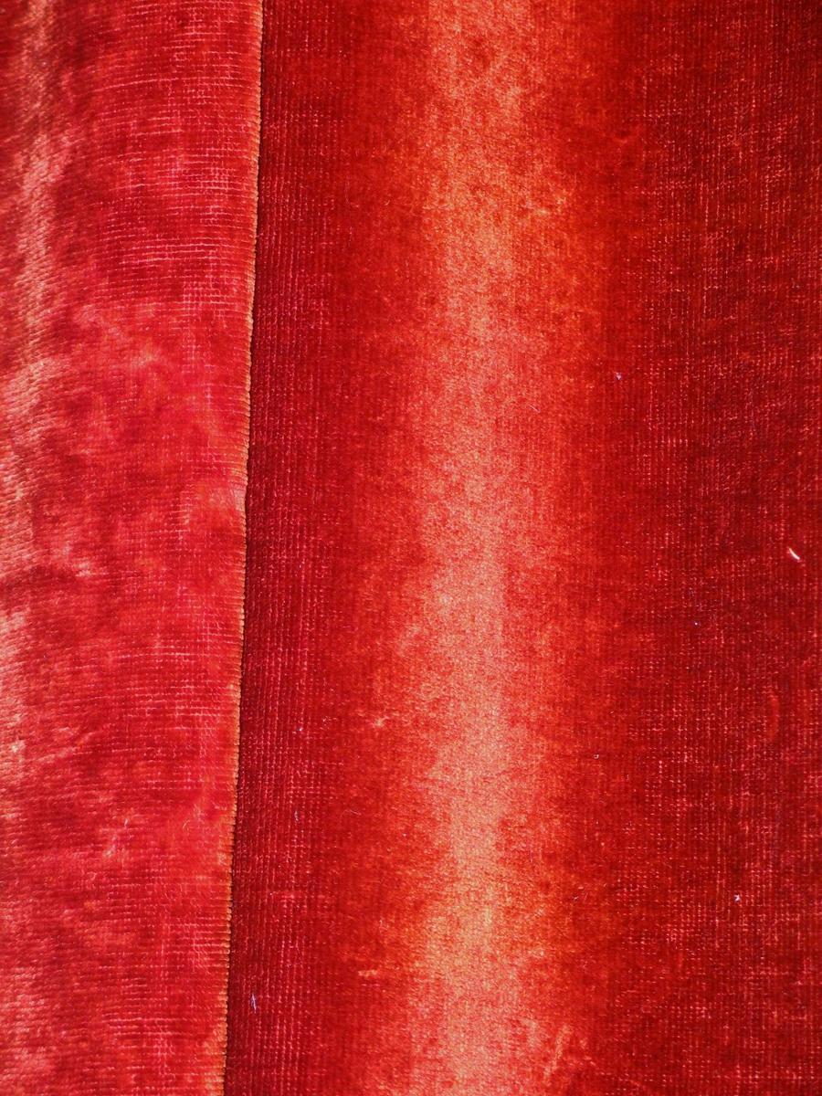 Rødbrun portiere i bomullsplysj.  Påsydd stykke av plysjen 70 cm høyt, 62 cm bredt for å skjule asbestforheng (t.h. f. piano). Ellers foret med grønt bomullsstoff. Isydd feste for metallringer, samtidig lagt en liten fold. Forhenget er hengt på kroker i en trelist.