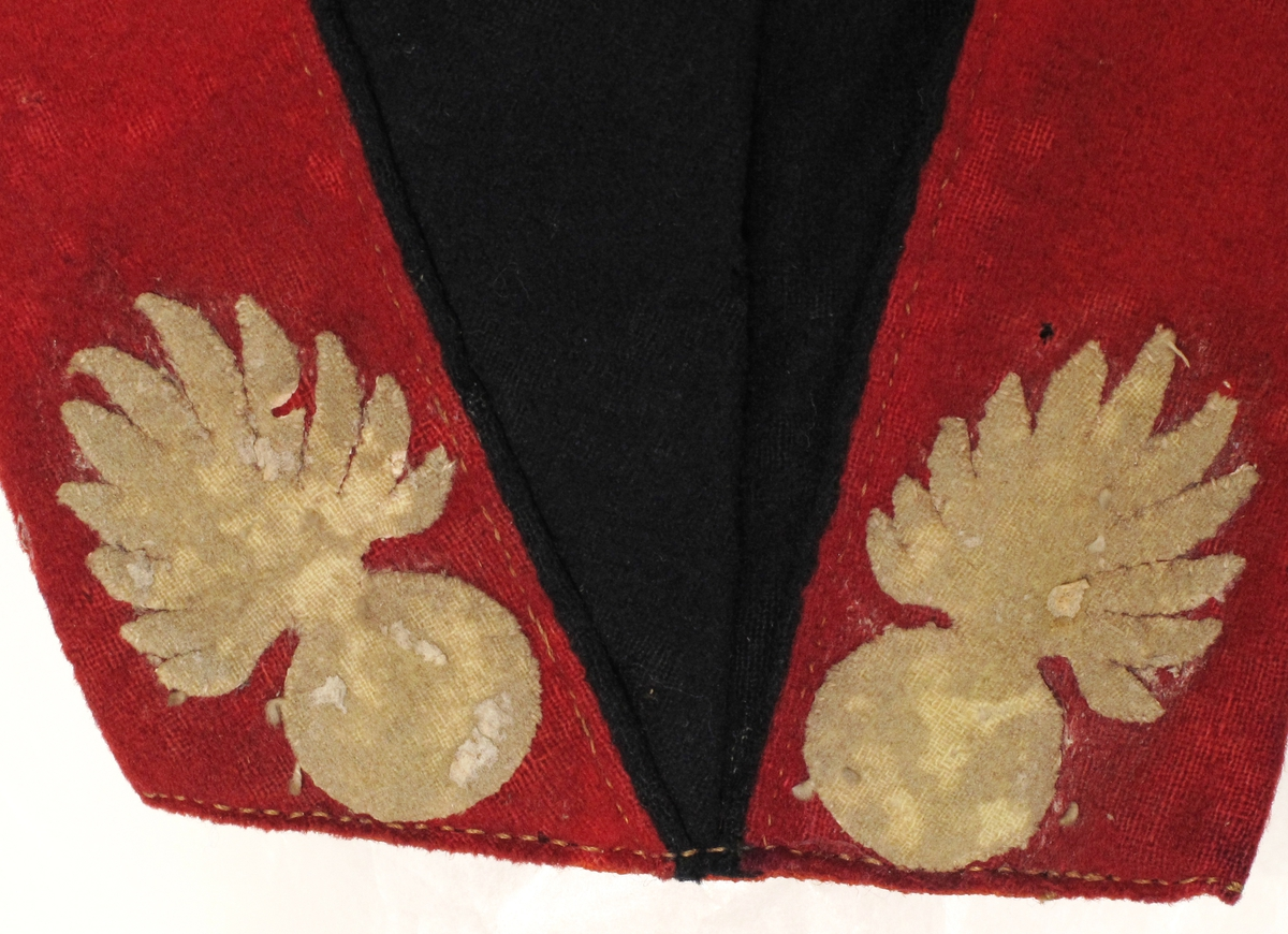 En brennende bombe er motiv på knappene og som applikasjon på uniformen. Dette er artelleriets merke.