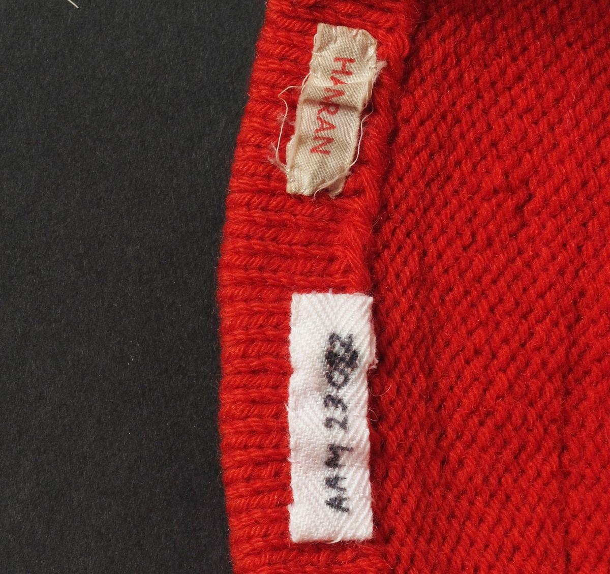 Nisselue, rød topplue.  Ull, rød,  strikket.   Barnetopplue,  forholdsvis lang og spiss.  Oppbrettet/fald sydd til med rød tråd.  To rader med fellinger.