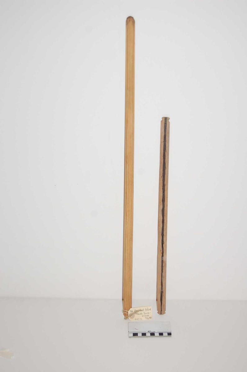 a;  flat under, overside tynnere kanter-3mm på hver side, buet i midten. b, skarpe sider, buet over og underside, mørk, ujevn stripe p den ene siden. To hakk nær hver ende, endene lett krumme