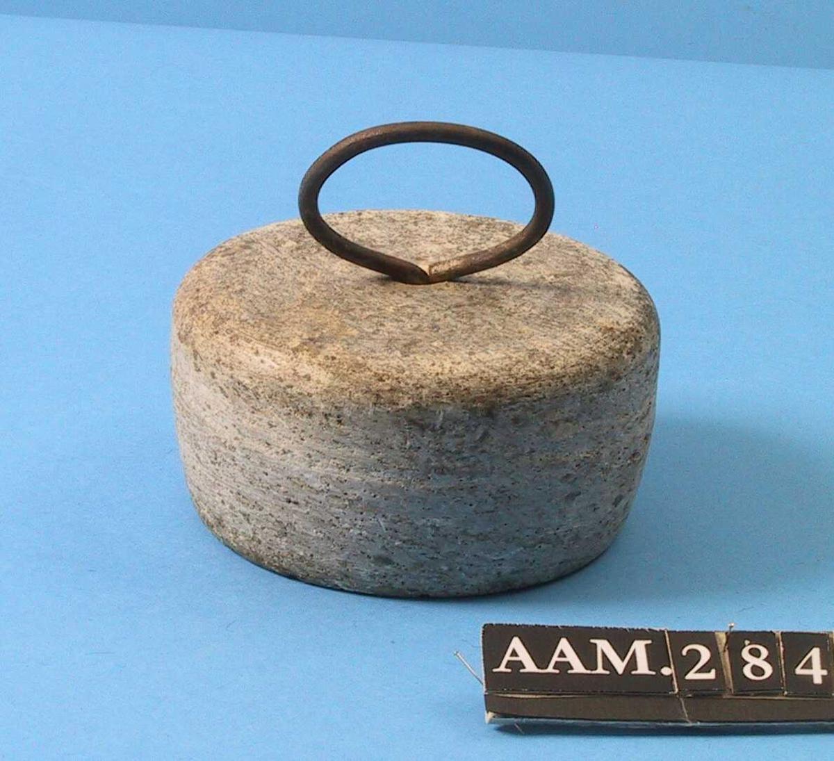 Rundt stykke kleberstein, med  øyeformet handtak av jern midt på.