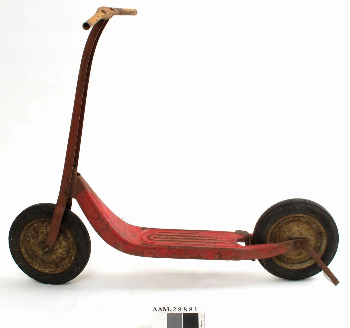 Sparkesykkel i sørmalt metall, grå hjul, sort helgummi. Sykkelen har støtte (bak), brems som betjenes med fotpedal, og riflet mønster i fotbrett. Noen rustflekker.