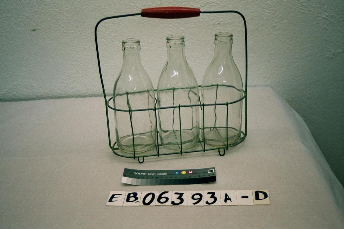 Form: avlang, oval kurv med tre rom til flasker, hank med rødt trehåndtak, tre flasker