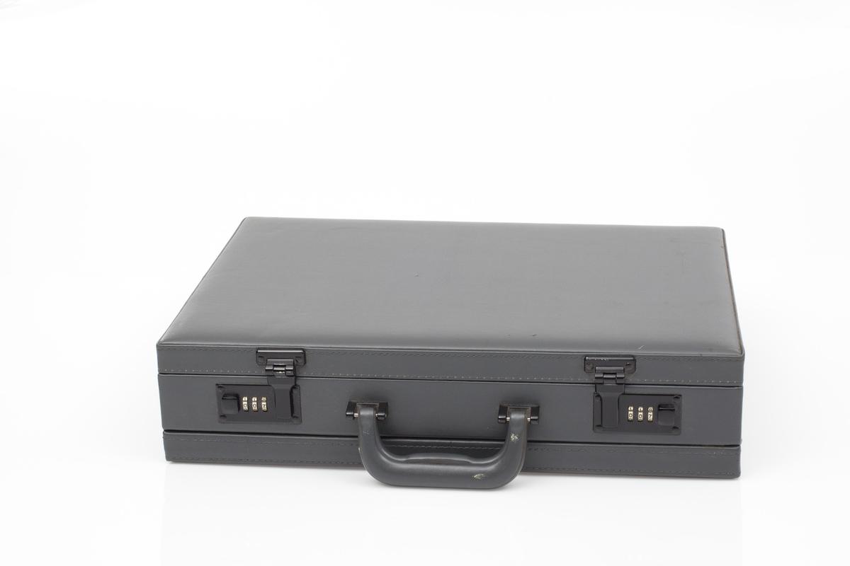 Vesken er hard og rektangulær. Den er i gråfarget imitert skinn. Den har to låsemekanismer med kode. Den har et håndtak. Inni i vesken er den foret med grå fløyel. Det er to lommer til dokumenter i lokket av vesken + to holdere for penner og to mindre lommer for kort olign.