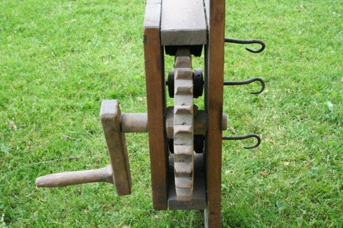 Planke med påmontert kasse. Inni denne 3 tannhjul som drives med en sveiv. De tre jernkrokene fungerer som akslinger for tannnhjulene. Kasse av furu, tannhjul og sveiv av bjørk. Føyd sammen med runde plugger.