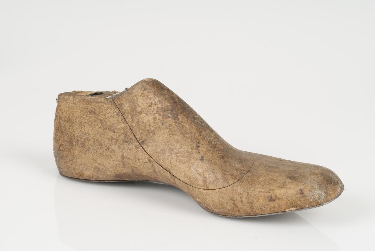 En tremodell i to deler; lest og opplest/overlest (kile). Venstrefot i skostørrelse 35, og 8 cm i vidde. Såle av metall.