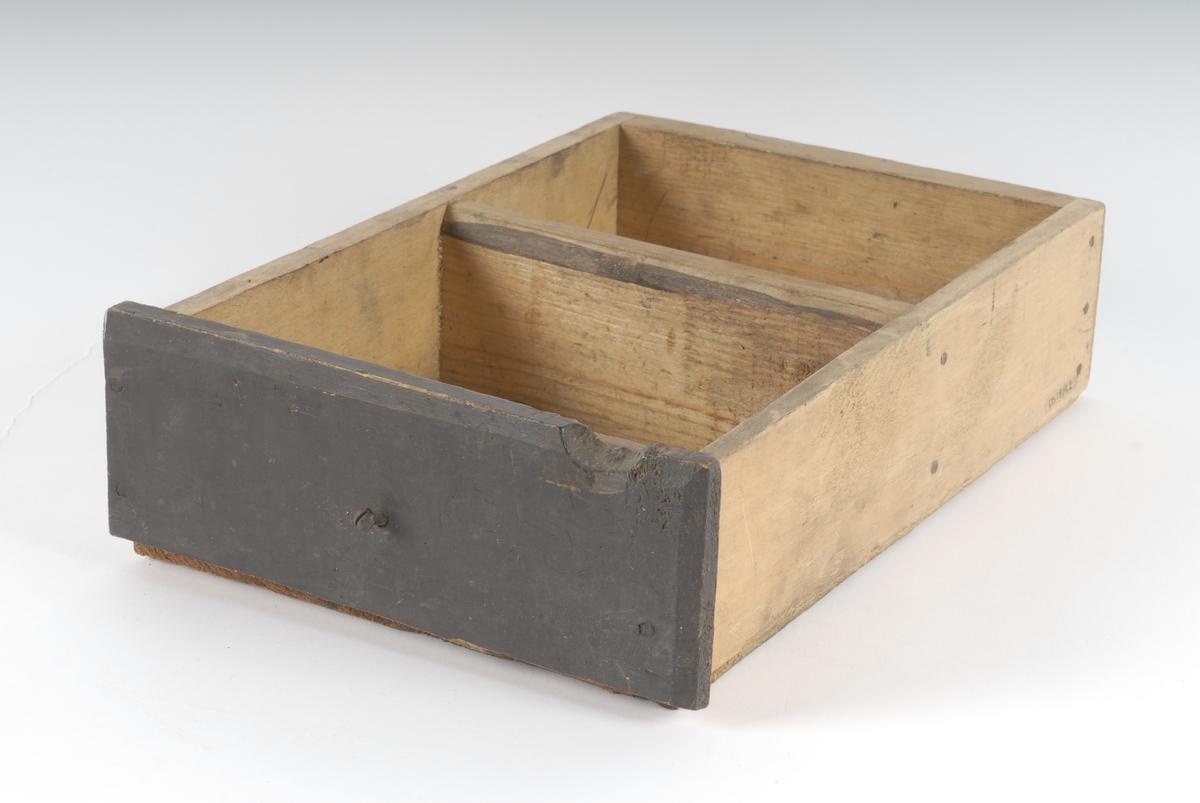 En treskuff som trolig tilhører et bord. Treskuffens forside er malt mørk brunt.
