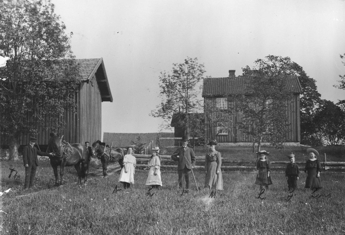 Sundby Østre. Familie samlet på jordet med hester.