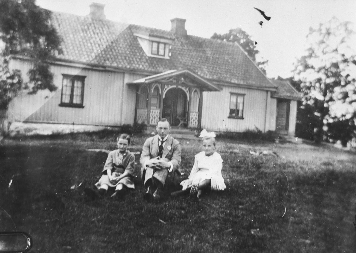 En mann og to jenter sitter i gresset foran et bolighus.