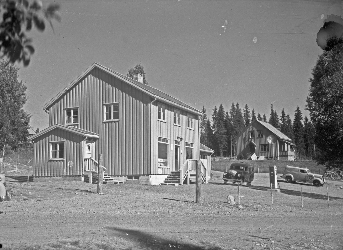 Hus med bensinpumpe og to biler fra 30-40 tallet utenfor. Bilene fra venstre: Austin A40 1949-54 modell og en Dodge 1936 modell.