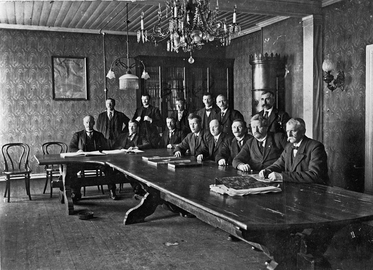 14 menn ved et stort bord.